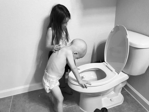 Cette poignante photo montre une fillette en train de soutenir son frère atteint de la