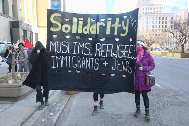 Protestors carry a large banner during a rally held in Toronto March 23,