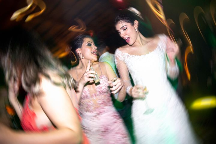 Bride and wedding guest dancing during a wedding reception.