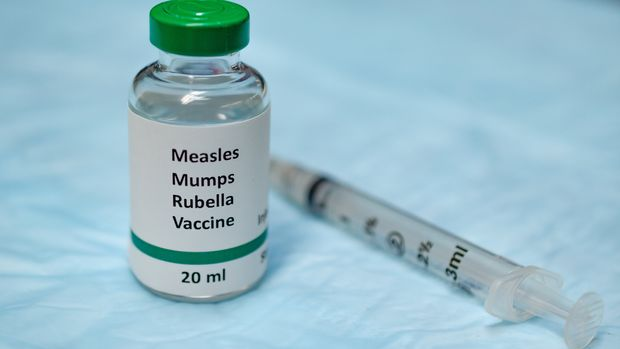 MMR vaccine holding in hand with injection syringe at the background