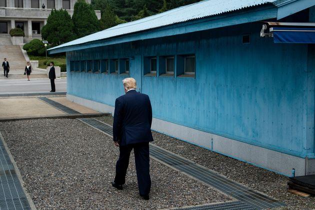 US President Donald Trump walks to the line of demarcation to meet North Korea's leader Kim Jong-un in...
