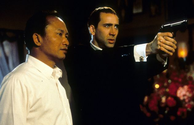 Director John Woo watches as Nicolas Cage aims pistol in between scenes from the film 'Face/Off', 1997....