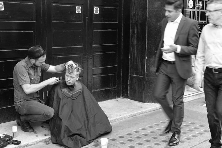 """""""A kind barber gives a free haircut to a homeless man outside Victoria station."""""""