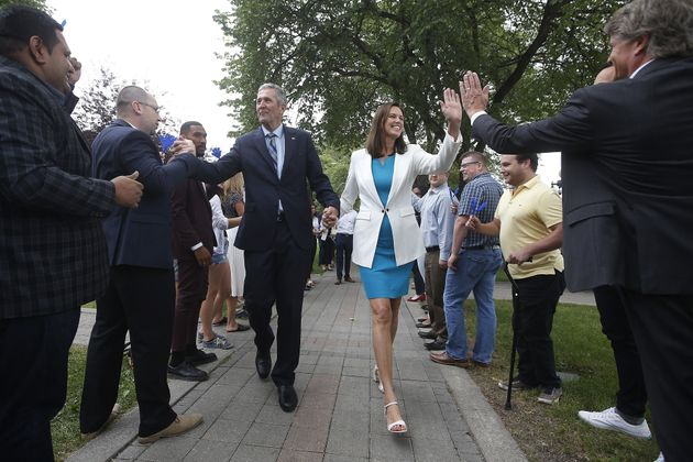 Manitoba Conservative Leader Brian Pallister and his wife, Esther, give high-fives to supporters before...
