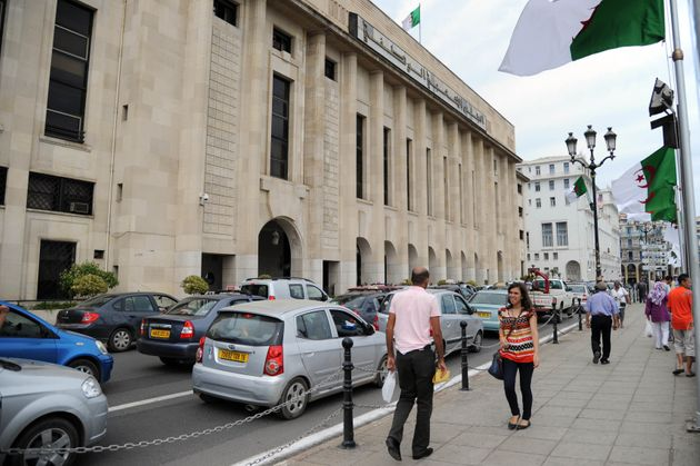 Algerians walk past the National Assembly building in the capital Algiers on September 3, 2012, as the...