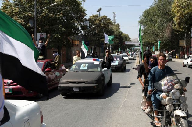 Afghans march in convoy with cars decorated with black flags and portraits of late Commander Ahmad Shah...