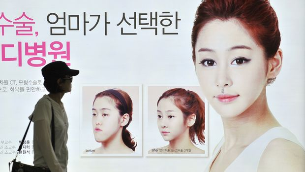 TO GO WITH Health-SKorea-cosmetic-surgery,FEATURE by Jung Ha-Won This picture taken on May 22, 2013 shows a South Korean woman walking past a street billboard advertising double-jaw surgery at a subway station in Seoul. South Korea's obsession with plastic surgery is moving on from standard eye and nose jobs to embrace a radical surgical procedure that requires months of often painful recovery. AFP PHOTO / JUNG YEON-JE        (Photo credit should read JUNG YEON-JE/AFP/Getty Images)