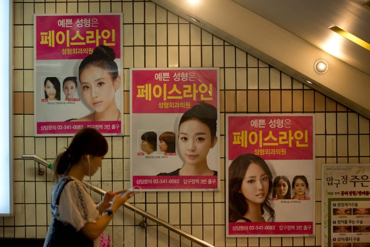 Advertisements for plastic surgery clinics are displayed at a subway station in Seoul.