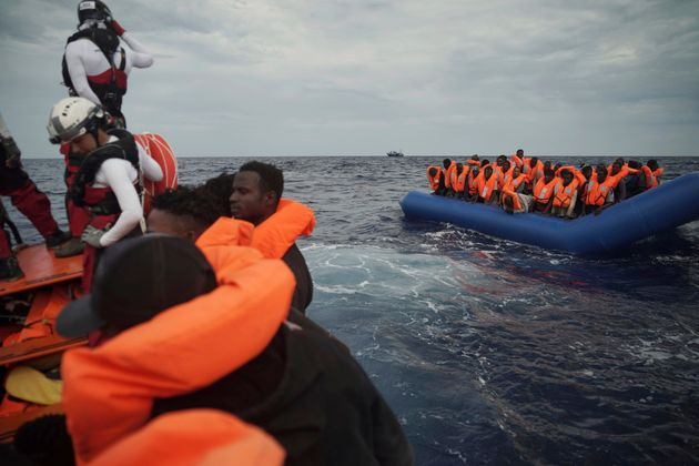 Migrants on a blue rubber boat wait to be rescued some 14 nautical miles from the coast of Libya in Mediterranean...