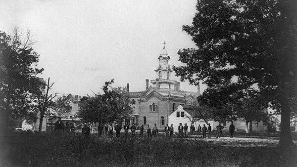 A Civil War-era image of Virginia Theological Seminary shows Union soldiers and black civilians standing in front of the semi