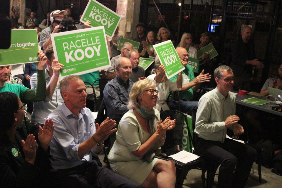Green Party leader Elizabeth May sits with candidates at a rally in
