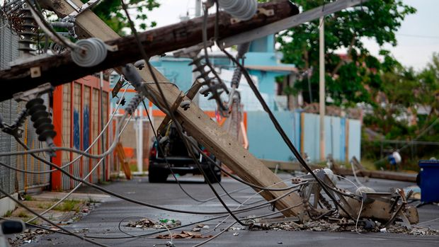 """Power line poles downed by the passing of Hurricane Maria lie on a street in San Juan, Puerto Rico on November 7, 2017.  The Center for Puerto Rican Studies at Hunter College in New York estimated in a report released last month that about 114,000 to 213,000 Puerto Rican residents will leave the island annually """"as a result of Hurricane Maria."""" / AFP PHOTO / Ricardo ARDUENGO        (Photo credit should read RICARDO ARDUENGO/AFP/Getty Images)"""