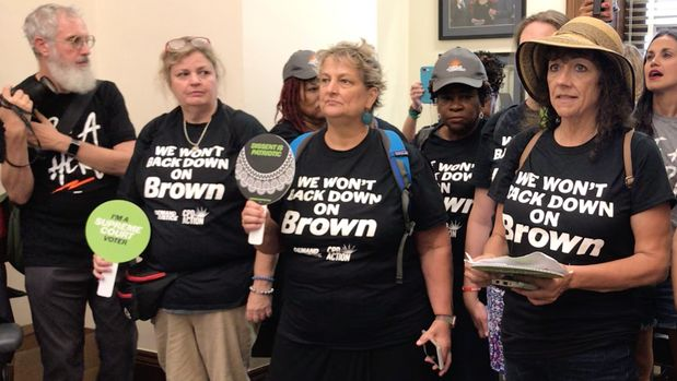 Protesters crash Sen. Chris Coon's office to urge him to stop voting to confirm Trump's judicial nominees who won't say if they think Brown v Board of Education was correctly decided.