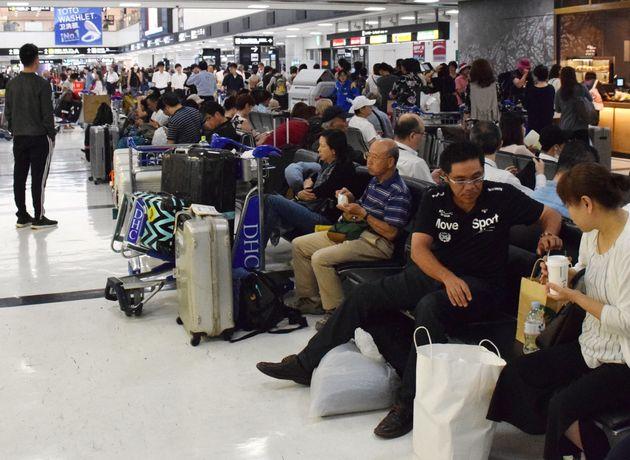 ロビーで一夜を明かし、電車やバスの出発を待つ利用客ら=9月10日、成田空港