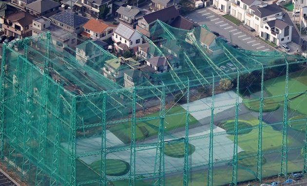 台風15号の影響で、住宅街に覆いかぶさるように倒れたゴルフ練習場のポールとネット=9月9日、千葉県市原市[時事通信ヘリより]