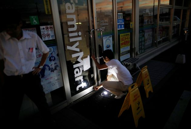 A man uses a flashlight as he locks up his shop during a blackout caused by Typhoon Faxai in Kisarazu,...
