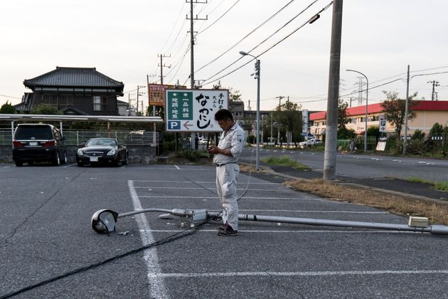 ICHIHARA, JAPAN - SEPTEMBER 09: A man stands next to a damaged street light following the passage of...