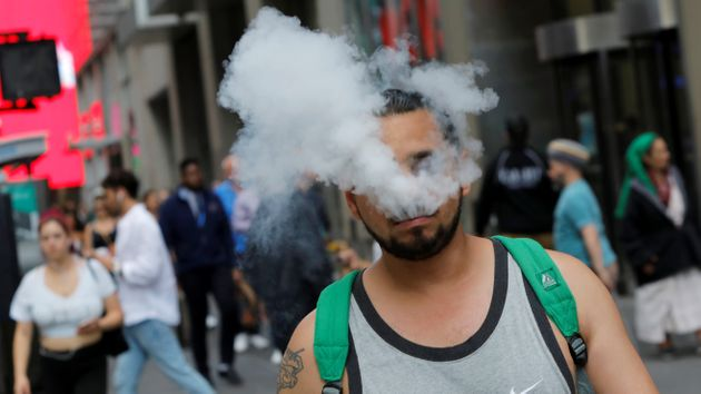 A man uses a vape as he walks on Broadway in New York City, U.S., September 9, 2019. REUTERS/Andrew