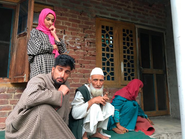 In this Monday, Aug. 26, photo, A Kashmiri man Mohammed Abdullah, center, sits with family members at their home and talks to reporters about his grandson who was picked up in a nocturnal raid recently and shifted to a jail in Agra.