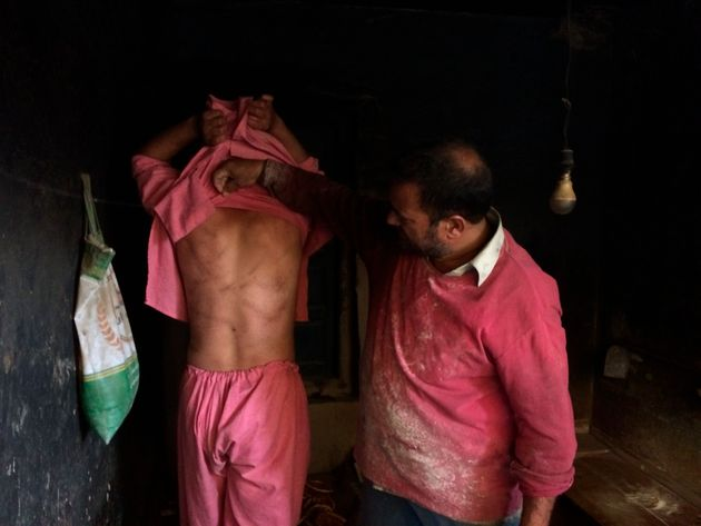 In this Monday, Aug. 26, 2019, photo, a Kashmiri baker Sonaullah Sofi lifts the shirt from his son's...
