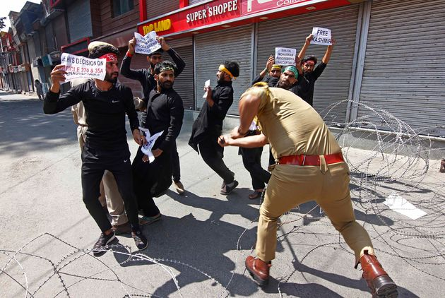 A police officer beats Kashmiri shiite muslims as they tried to took out a Muharram procession in Srinagar,...