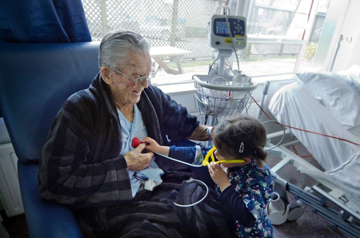 Small girl measuring heart beats to her sick grandfather with a toy stethoscope.