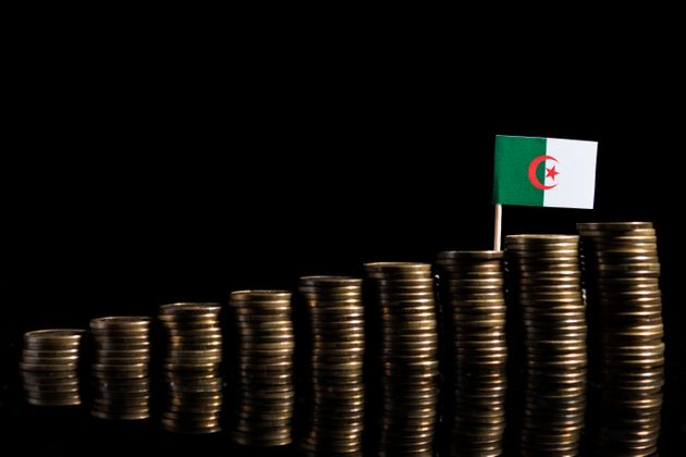 Algerian flag with lot of coins isolated on black