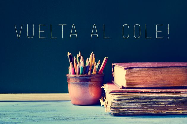 some pencils in a pot, some old books on a blue school desk, and the text vuelta al cole, back to school...