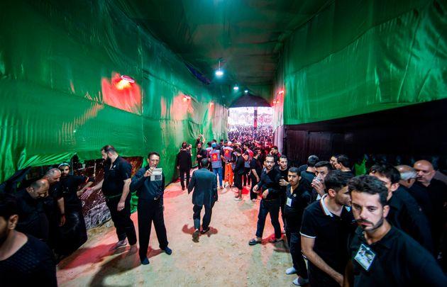 Shiite Muslim pilgrims walk through the the Bab al-Raja gate of the courtyard of the Imam Hussein shrine...