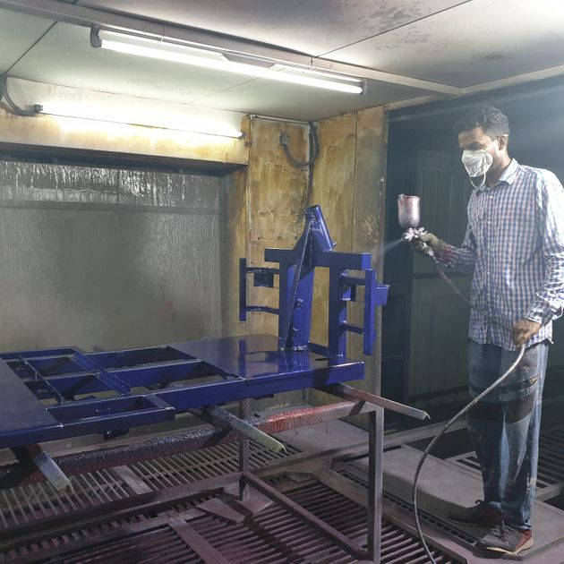 A worker painting the chassis of an e-rickshaw at an electric vehicle manufacturing company in Zirakpur,
