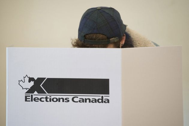 A woman marks her ballot behind a privacy barrier in the riding of Vaudreuil-Soulanges, west of Montreal,...