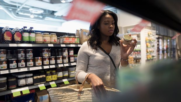 Young woman grocery shopping, reading label on jar in market aisle
