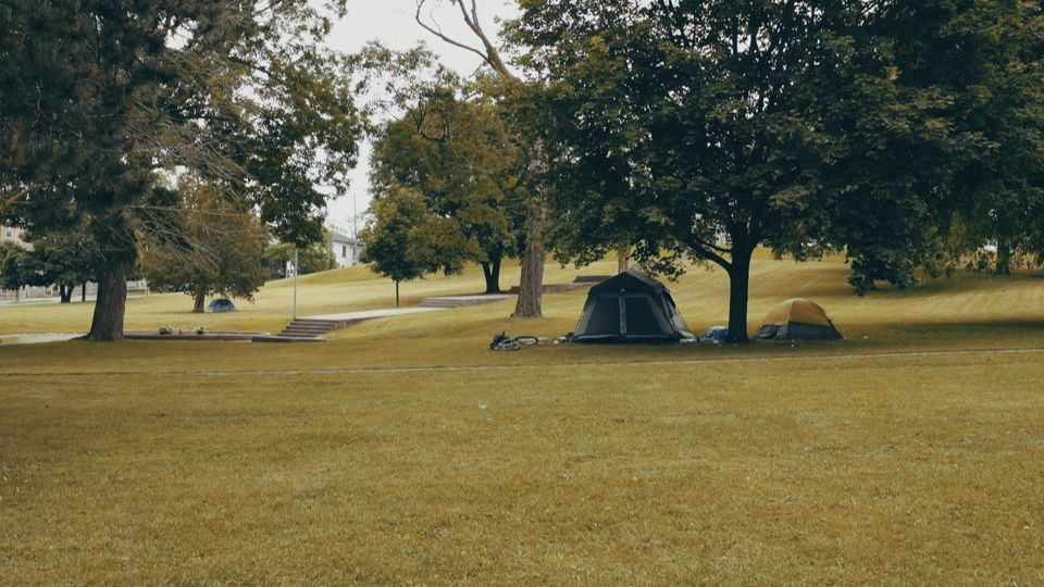 People sleep in tents in Victoria Park, a grassy square city block with mature trees across the street...