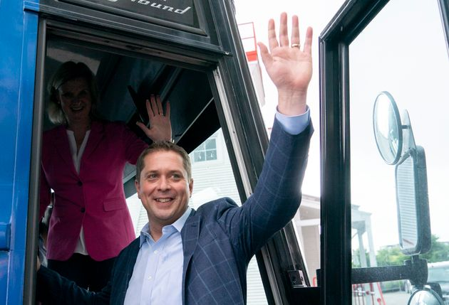 Conservative leader Andrew Scheer wavs tot he crowd as he and his wife Jill board the campaign bus following...