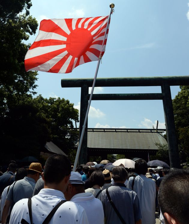 A Rising Sun flag is hoisted as people enter the controversial Yasukuni shrine to honour the dead to...