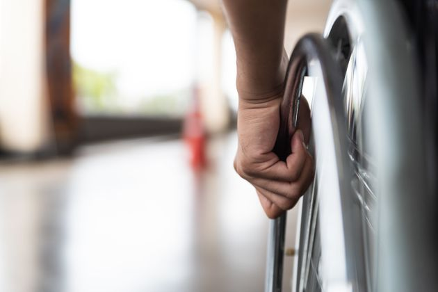 closeup disabled man hand on wheel of
