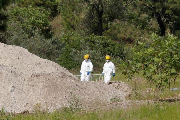 Peritos forenses trabajando en la fosa clandestina junto a maquinaria