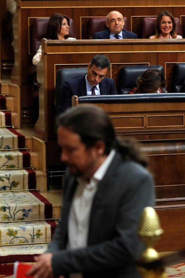 El líder de Unidas Podemos, Pablo Iglesias, pasa por delante del presidente del Gobierno en funciones,...