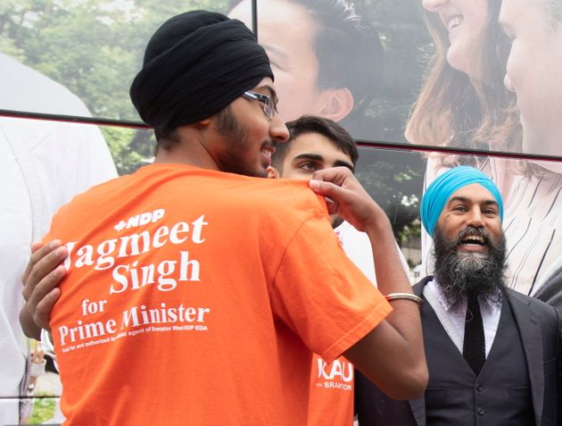 NDP Leader Jagmeet Singh laughs as he reads the slogan on a volunteer's shirt while taking photos following...