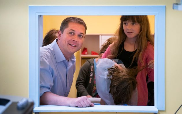 Conservative leader Andrew Scheer peers through the window of a playhouse while visiting a daycare in...
