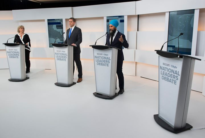 A empty podium is pictured as Green Party Leader Elizabeth May, left, Conservative Leader Andrew Scheer, centre, and NDP Leader Jagmeet Singh take part during the Maclean's/Citytv debate.