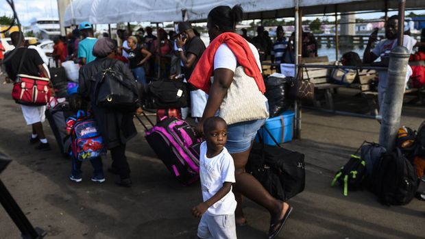 "Evacuees wait to board a bus heading to an evacuation shelter after getting off a ferry from Marsh Harbour on Abaco island in the aftermath of hurricane Dorian in Nassau, Bahamas on September 9,2019 - President Donald Trump said Monday that the US would have to be careful about allowing Bahamian survivors of Hurricane Dorian into the country, warning there could be ""very bad people"" among them. The previous day, several hundred storm survivors were prevented from boarding a ferry from the Bahamas to Florida because they lacked US visas -- an incident that a top American immigration official said was a mistake. (Photo by ANDREW CABALLERO-REYNOLDS / AFP)        (Photo credit should read ANDREW CABALLERO-REYNOLDS/AFP/Getty Images)"
