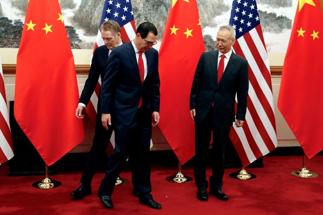 Chinese Vice Premier Liu He, right, looks as U.S. Treasury Secretary Steven Mnuchin, center, changes...