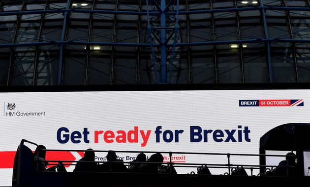 A bus passes an electronic billboard displaying a British government Brexit information awareness campaign...