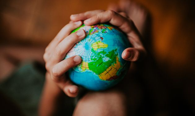 Child's hands holding a globe, space for