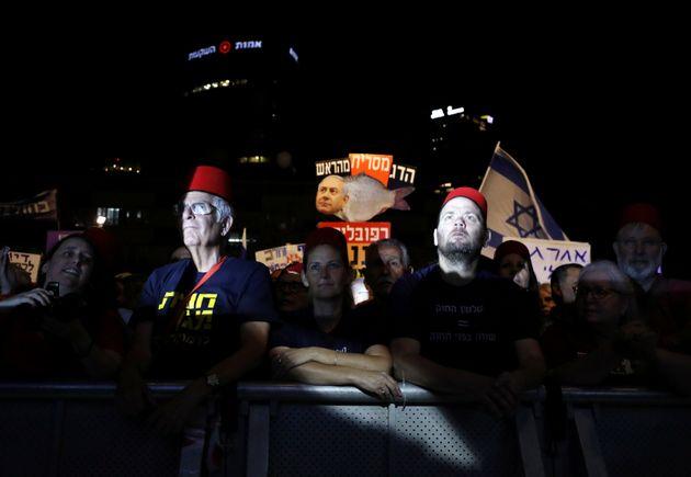 """Αντικυβερνητική συγκέντρωση στο Τελ Αβίβ. Οι διοργανωτές της συγκέντρωσης φρόντισαν να εφοδιάσουν τους χιλιάδες παρευρισκόμενους με κόκκινα οθωμανικά φέσια, παραπέμποντας άμεσα στο καθεστώς του ″άβουλου υπηκόου"""""""