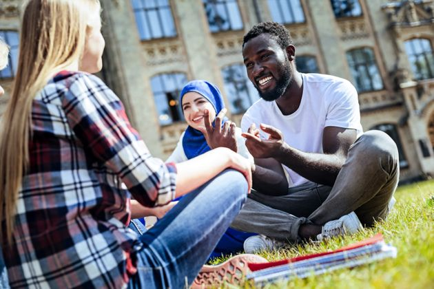 Pleasant conversation. Low angle shot of young people grinning broadly while sitting on grass and chatting...