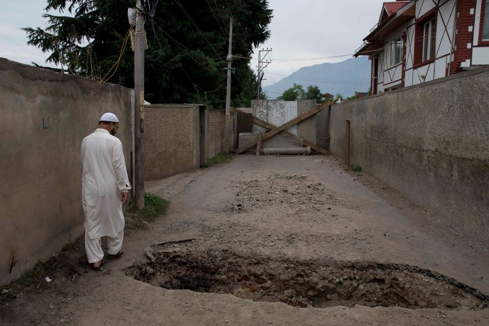 A Kashmiri man walks past a crater dug up by locals to prevent police vehicles enter the area amid curfew-like...