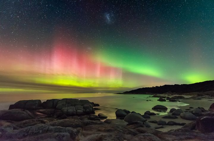 Aurora Australis from Beerbarrel Beach, by James Stone.<br /><br />A brightly coloured display of the Southern Lights beams high into the night sky on the east coast of Tasmania. The Large Magellanic Cloud also appears at the top centre of the image. Deserted beaches and minimal light pollution make Tasmania an ideal place to photograph the night sky, even more so when the aurora comes out to play.