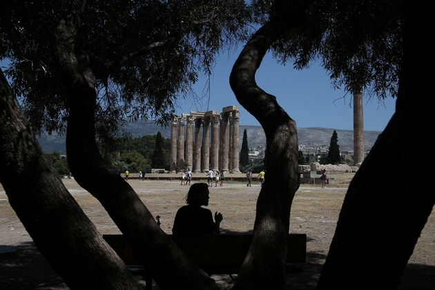 A tourist sits under the shadow of a tree during a hot day, at the archaeological site of the Temple...